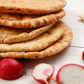 A stack of pitas on a wooden table.